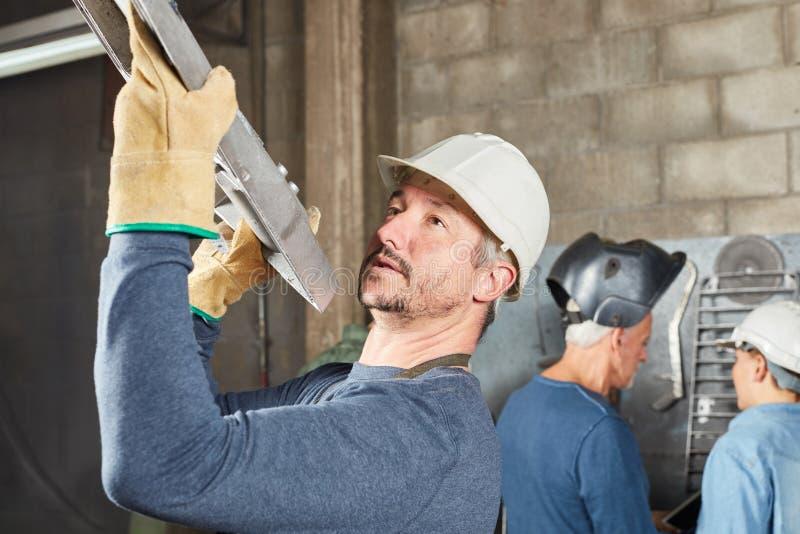 De arbeider draagt metaal of ijzerwerkstuk royalty-vrije stock fotografie