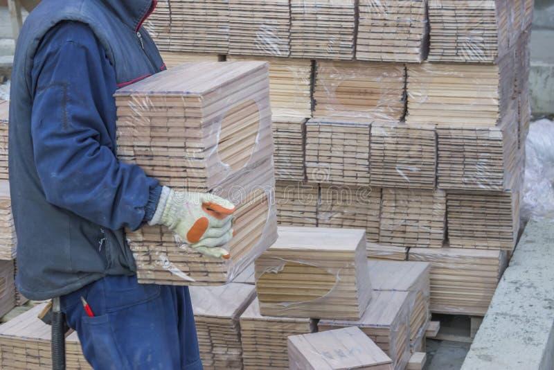De arbeider draagt pakketten van beukehoutprofielen 3 stock afbeeldingen