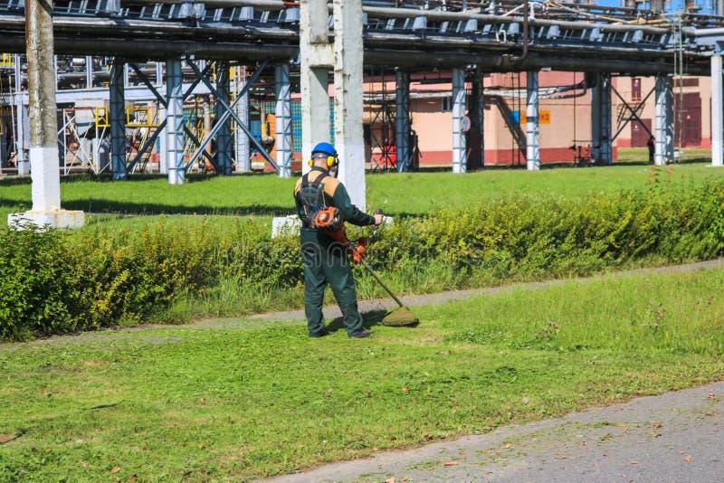 De arbeider in een beschermend kostuum en een masker gebruikt een speciaal apparaat om het gras op een zonnige de zomerdag te maa stock fotografie