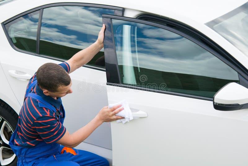 De arbeider in een blauw kostuum, veegt de auto met een wit vod af royalty-vrije stock fotografie