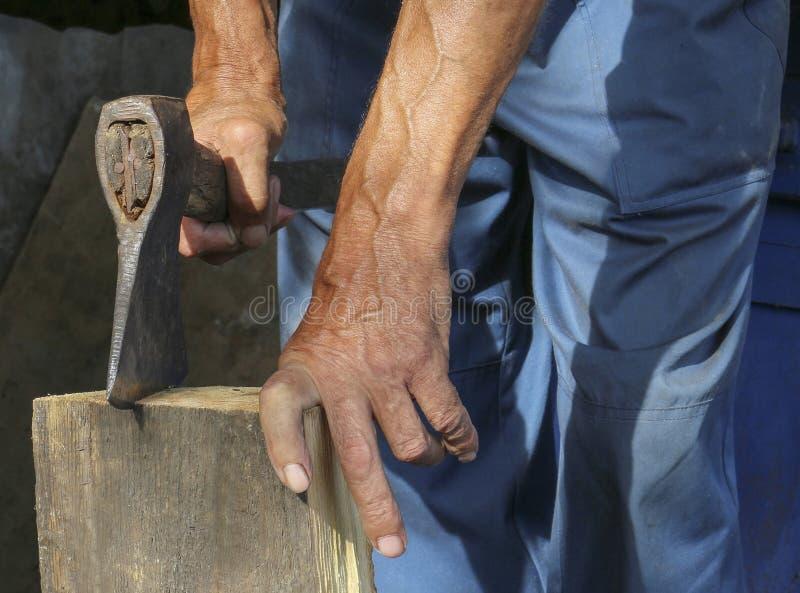 De arbeider, een mens met een bijl hakkend brandhout werknemer royalty-vrije stock foto