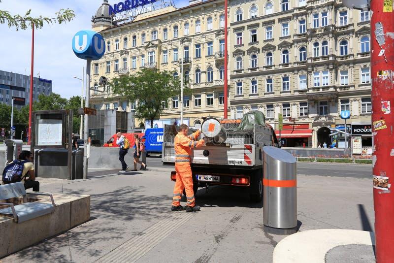 De arbeider in een oranje uniform maakt een vuilnisbak in de vuilnisauto leeg Stad van Wenen, Oostenrijk royalty-vrije stock afbeelding