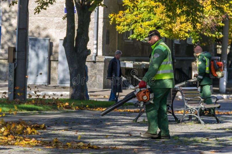 De arbeider gebruikt een ventilator om gevallen de herfstbladeren in een openbaar park te ontruimen stock afbeelding