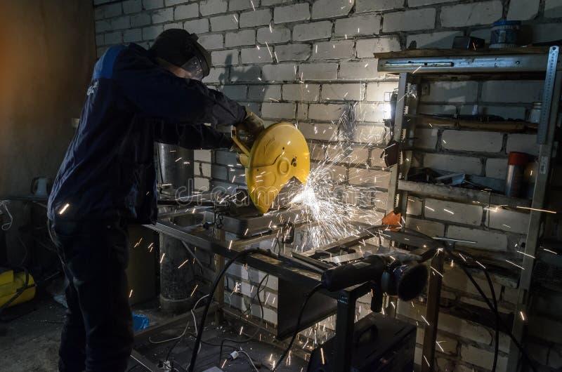 De arbeider houdt handen de metallpijp om het op de machine te snijden Tegen de achtergrond van witte bakstenen royalty-vrije stock fotografie