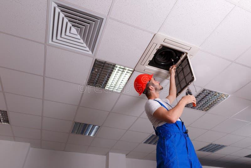 De arbeider inspecteert de bedrading voor ventilatie royalty-vrije stock afbeelding