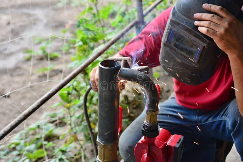 De arbeider kookt de het verwarmen pijp, die verbinding lassen Het voorbereidingen treffen voor de winter het verwarmen royalty-vrije stock foto
