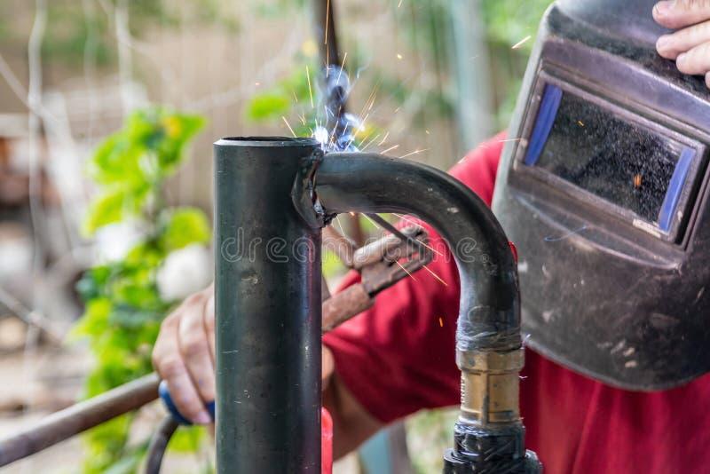 De arbeider kookt de het verwarmen pijp, die verbinding lassen Het voorbereidingen treffen voor de winter het verwarmen royalty-vrije stock fotografie