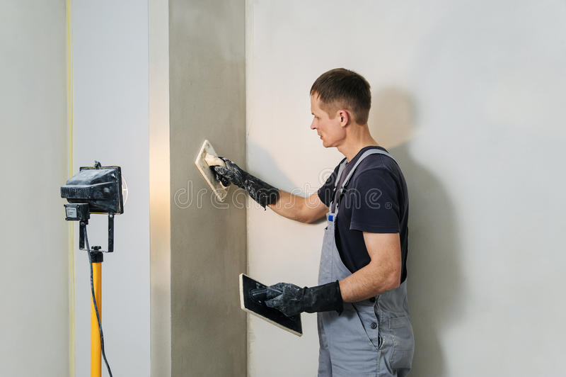 De arbeider maakt definitief het gladmaken pleister op de muur stock foto's