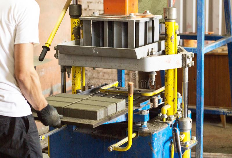 De arbeider maakt een stoeptegel achter de machine, een close-up, het bedekken plak, vervaardiging van het bedekken plakken stock foto's