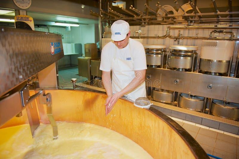 De arbeider maakt kaas bij een kaasfabriek in Gruyeres, Zwitserland royalty-vrije stock afbeeldingen