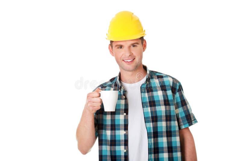 De arbeider op een onderbreking drinkt koffie stock afbeelding