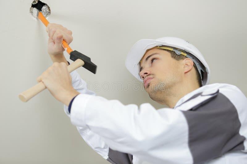 De arbeider schaaft oude verf op plafond stock foto's