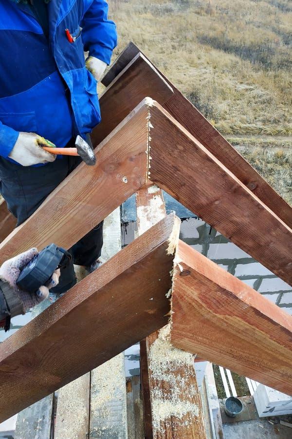 de arbeider schiet de daksparren op het dakkader stock afbeelding