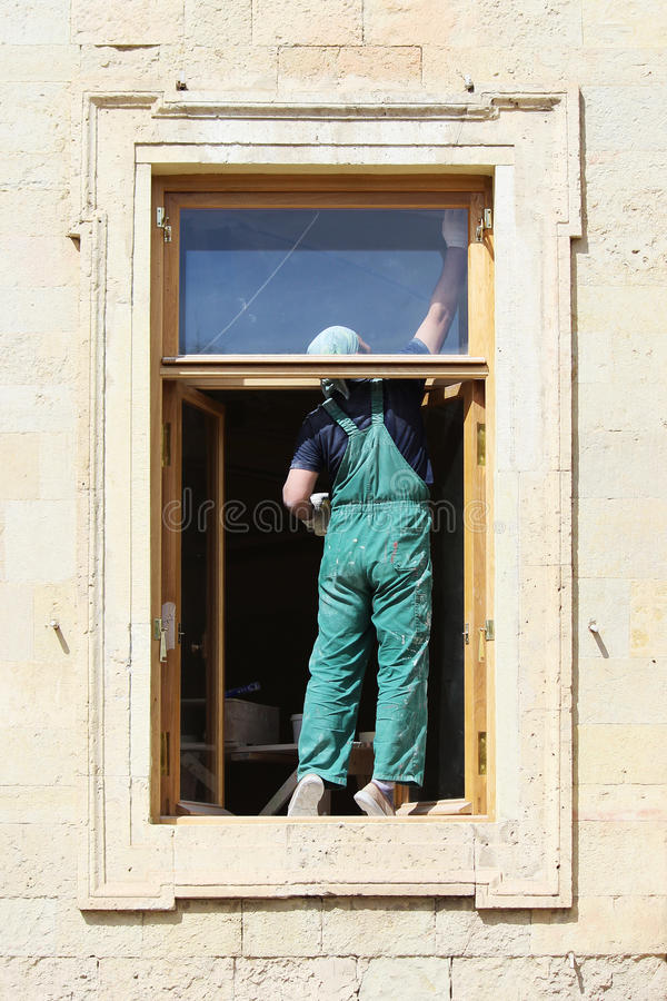 De arbeider schildert een houten raamkozijn in het Gatchina-Paleis stock afbeeldingen