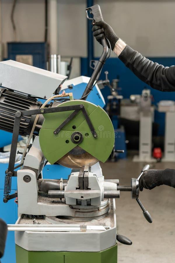 De arbeider snijdt een stuk van materiaal met een cirkelzaagmachine Industriële ingenieur die bij het snijden van een metaal en e stock foto's