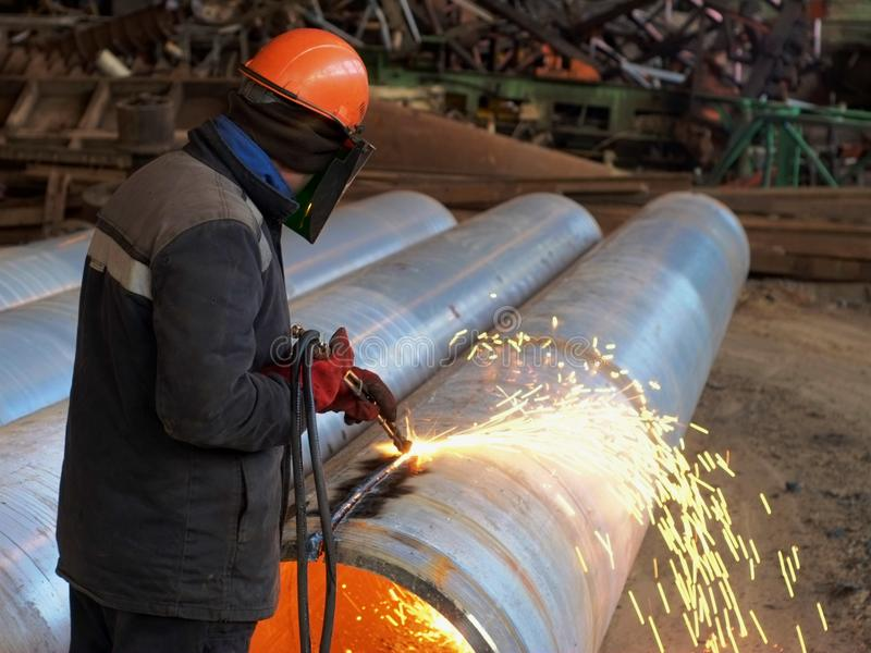 De arbeider snijdt de pijp met een gassnijder royalty-vrije stock foto's