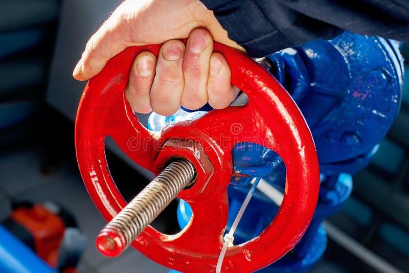 De arbeider spint de rode klep en sluit de gaslevering af Hand en klepringsclose-up royalty-vrije stock foto's