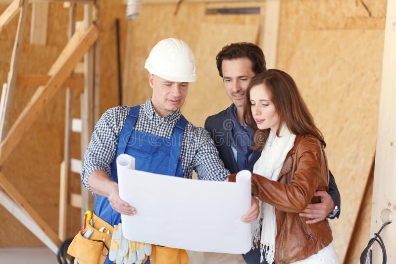 De arbeider toont de plannen van het huisontwerp stock afbeeldingen