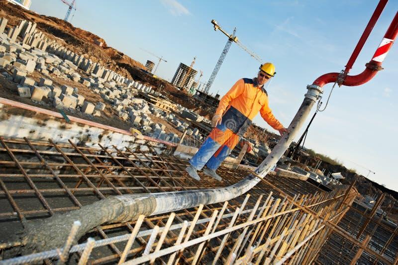 De arbeider van de bouwer aan het concrete gietende werk stock afbeelding