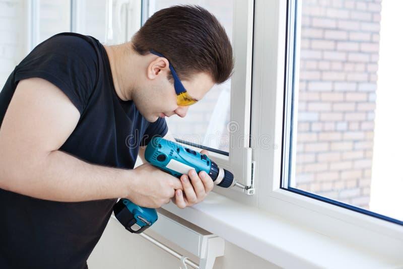 De arbeider van de mens het opzetten venster stock foto's