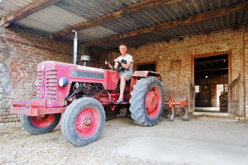 De arbeider van het landbouwbedrijf op Tractor stock fotografie