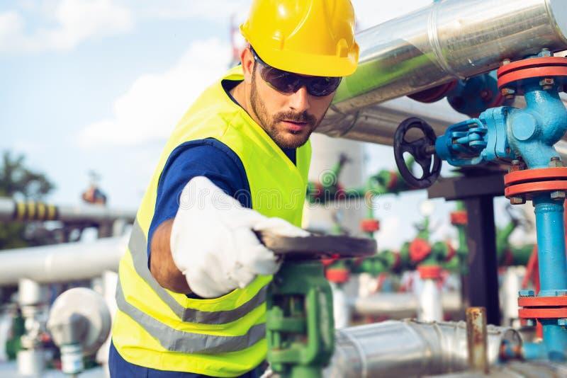 De arbeider van de olie het draaien klep op booreiland royalty-vrije stock afbeeldingen