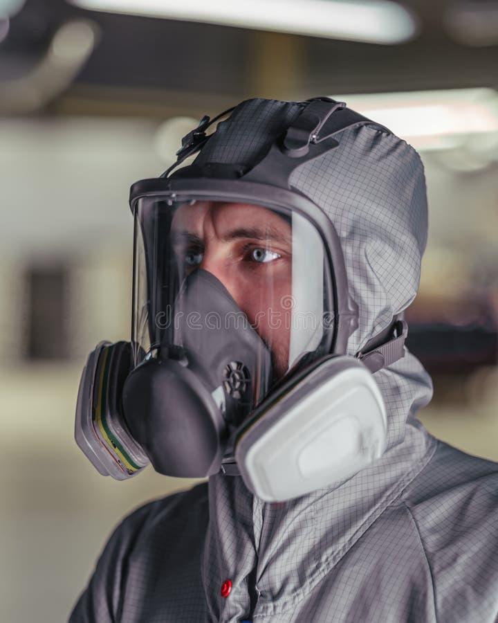 De arbeider van winkel van kleuring in overall en een beschermend masker stock fotografie