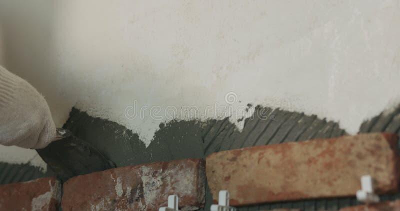 De arbeider verwijdert bovenmatige concrete lijm aan muur alvorens baksteentegel toe te passen royalty-vrije stock foto's