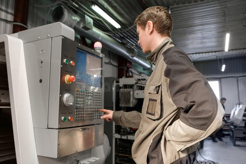 De arbeider verwijdert het deel uit CNC draaibankmachine Het draaien machine om met het boorhulpmiddel en het hulpmiddel van de c royalty-vrije stock afbeeldingen