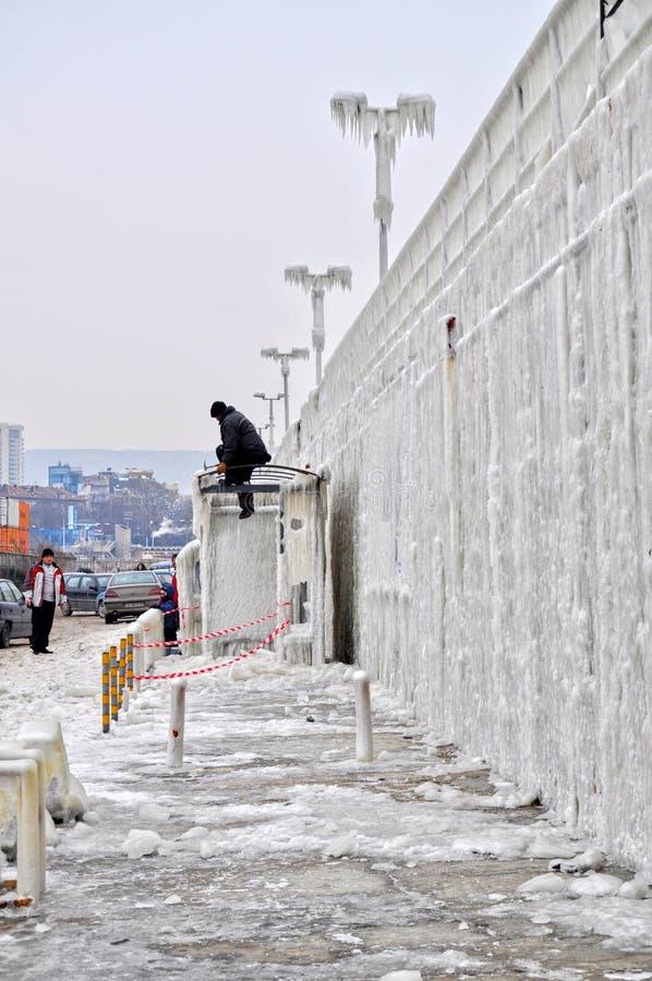 De arbeider verwijdert ijs uit berijpte bushalte royalty-vrije stock fotografie