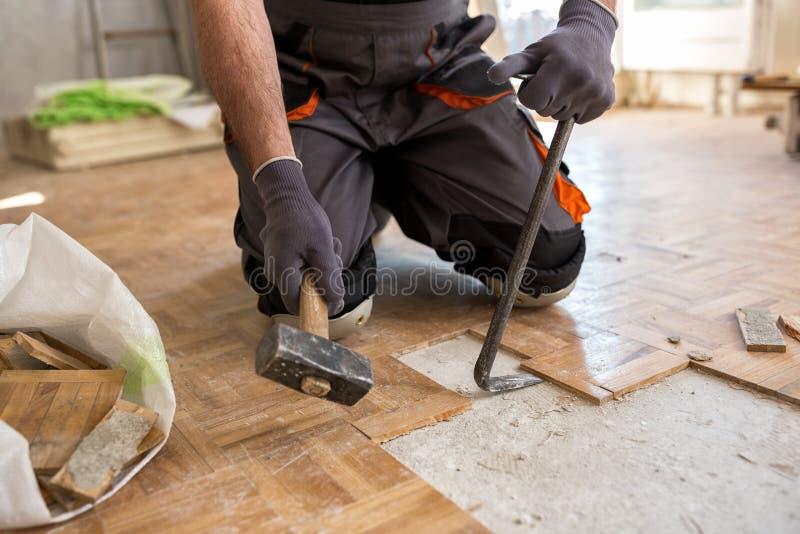 De arbeider verwijdert oude fparquet, vernieuwingshuis stock foto's