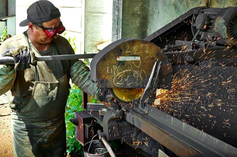 De arbeider voert het werk aangaande metaal, vonken uit royalty-vrije stock afbeelding