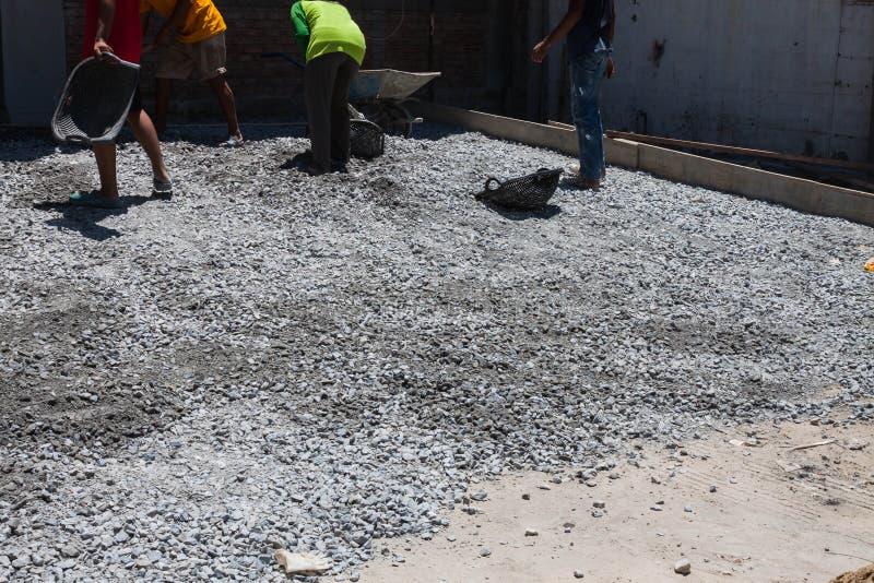 De arbeider zal sorterend steen in grondplak verpletteren stock fotografie