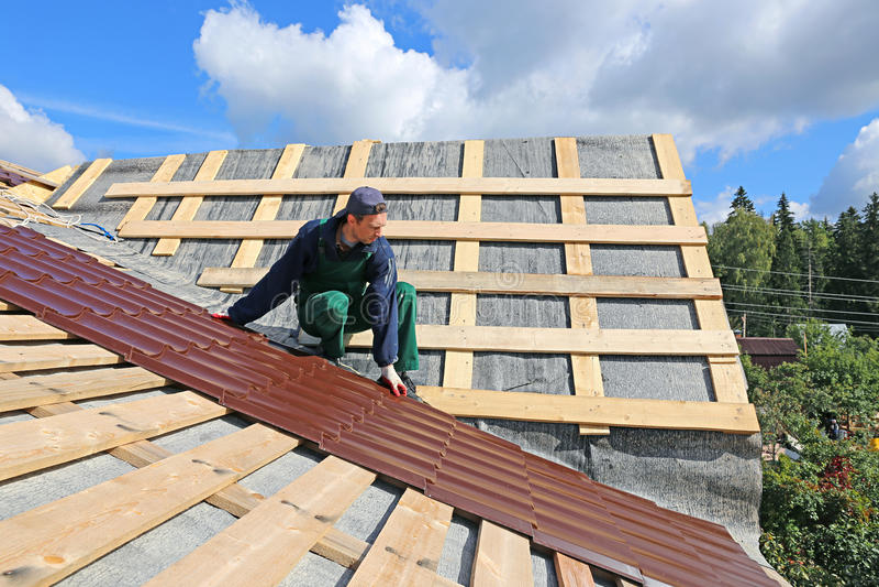 De arbeider zet de metaaltegels op het dak royalty-vrije stock foto