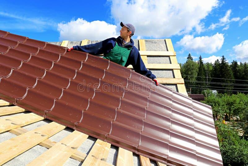De arbeider zet de metaaltegels op het dak stock afbeelding