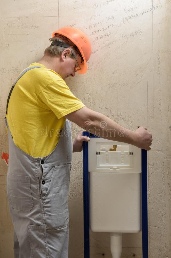 De arbeider zet een ingebouwde toilettank op stock afbeeldingen