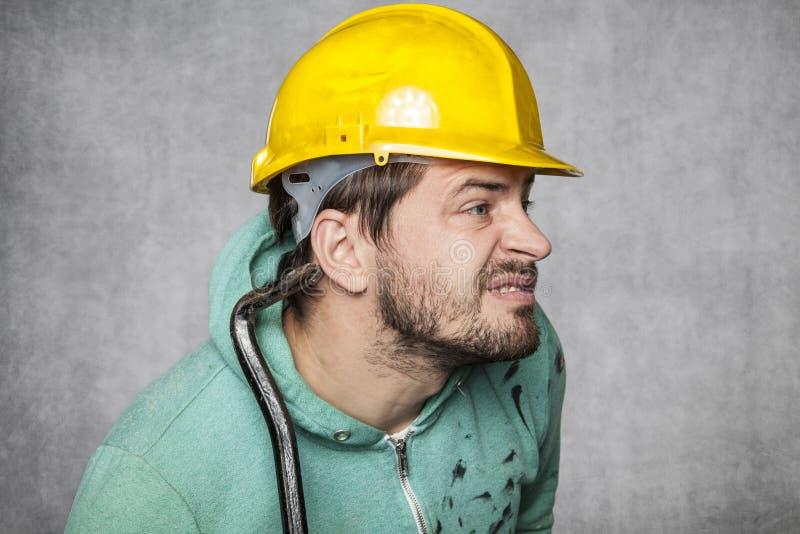 De arbeider zet een oor op om op anderen af te luisteren stock foto's