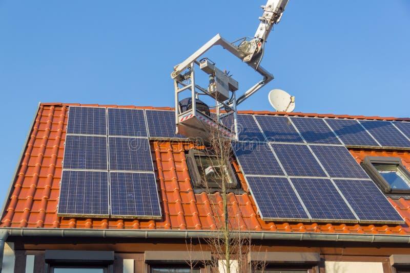 De arbeider zet een photovoltaic systeem op een dak op stock foto