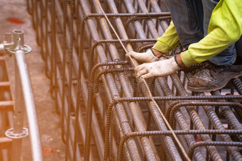 De arbeider zette groen veiligheidsoverhemd, gebruikt een zacht ijzer, bindt een grote staaldraad in het gebied dat een groot geb stock fotografie