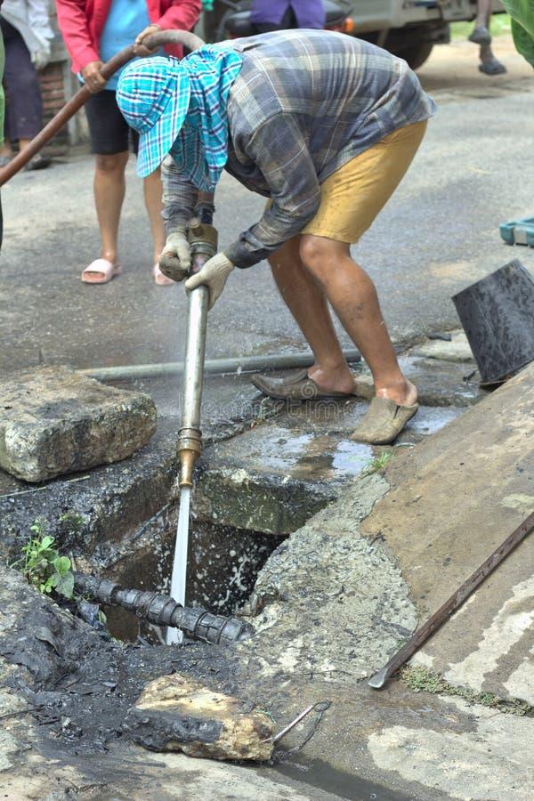 De arbeiders bespuiten water van een brandslang in een afvalwatervijver voor het schoonmaken stock foto's