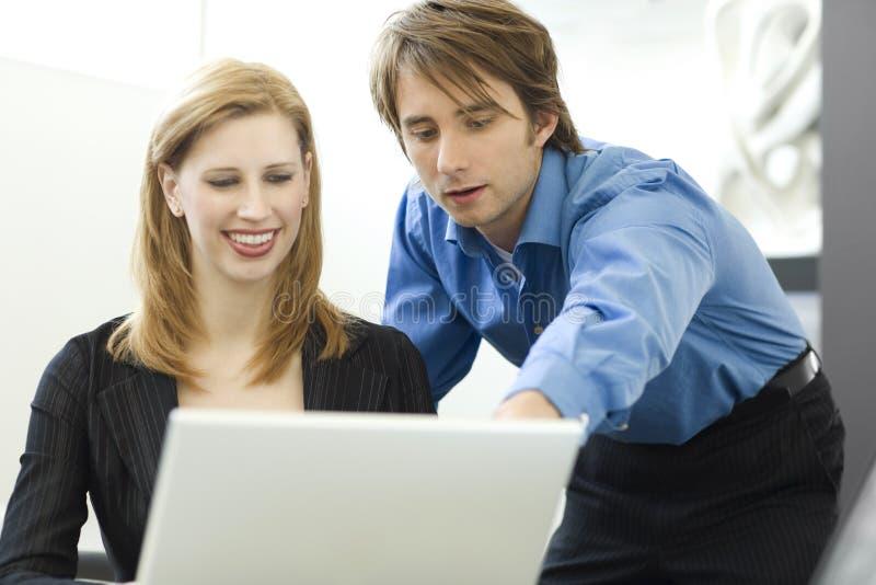 De arbeiders delen een computer stock fotografie