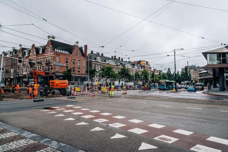 De arbeiders die de tram herstellen volgt in de straten van Amsterdam een bewolkte en regenachtige dag stock afbeeldingen