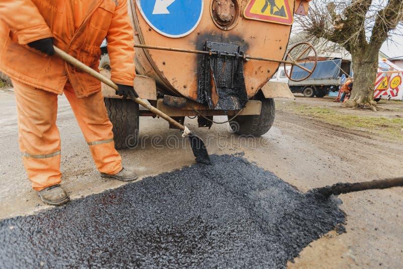 De arbeiders die de weg met schoppen herstellen vullen de reparatie van de asfaltoprijlaan stock fotografie