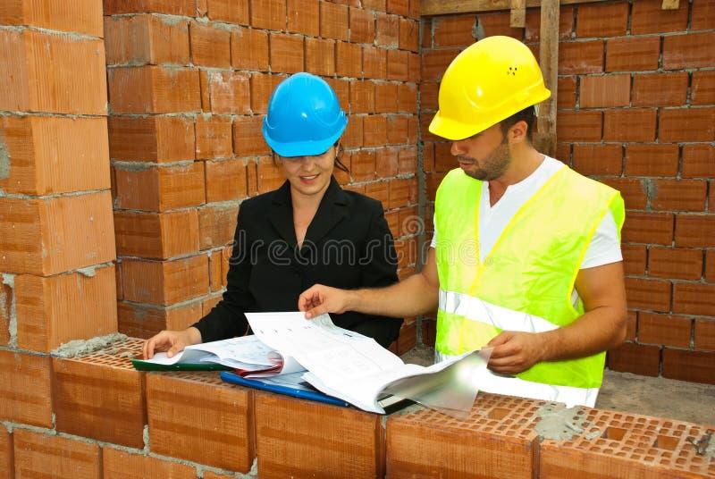 De arbeiders die van de bouw op huisplannen kijken