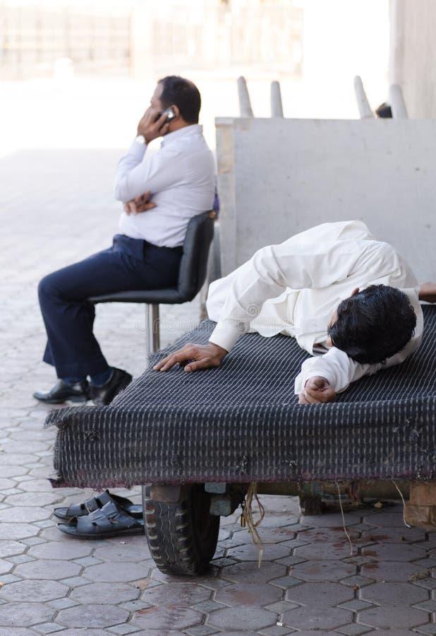 de arbeiders die van Doubai souk een slaap van de onderbrekingstijd in de dag, de V.A.E nemen stock fotografie