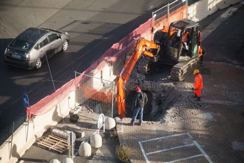 De arbeiders graven gat in asfalt met graafwerktuig stock fotografie
