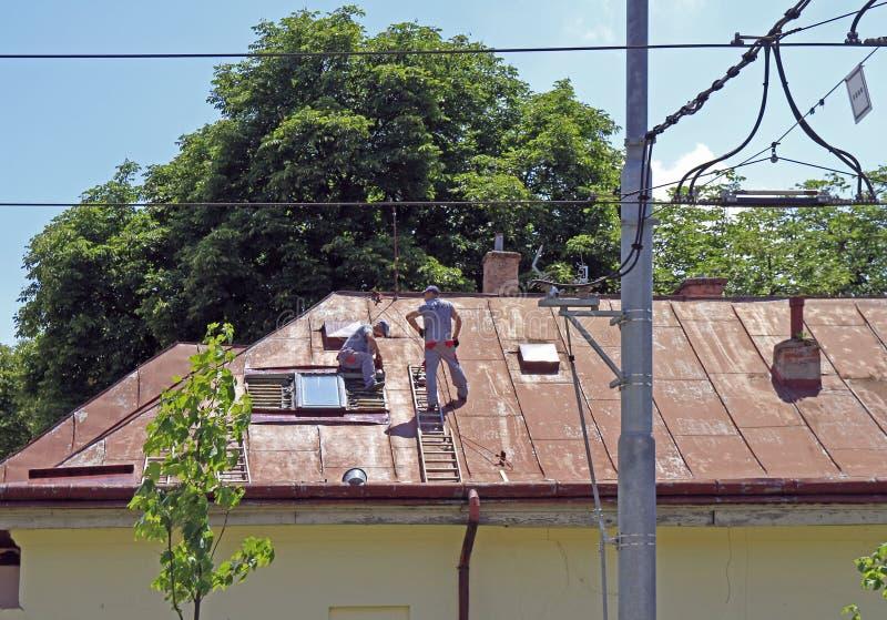 De arbeiders herstellen het dak van de bouw stock foto's