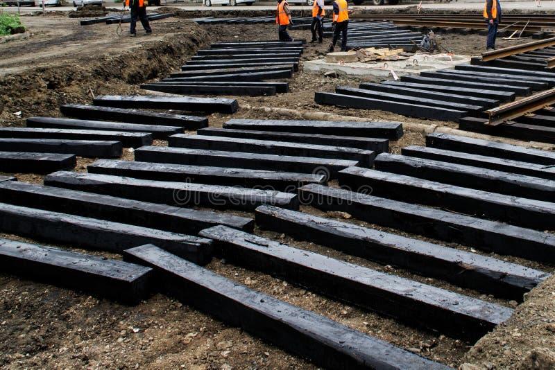 De arbeiders installeren in een geul zwarte houten dwarsbalken voor tramsporen Reparatie van de stadsweg stock foto's