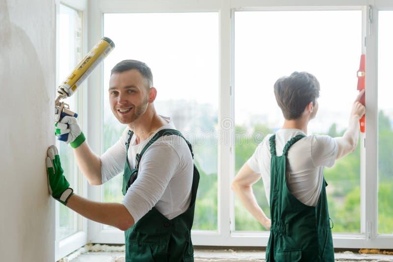 De arbeiders installeren een venster stock foto