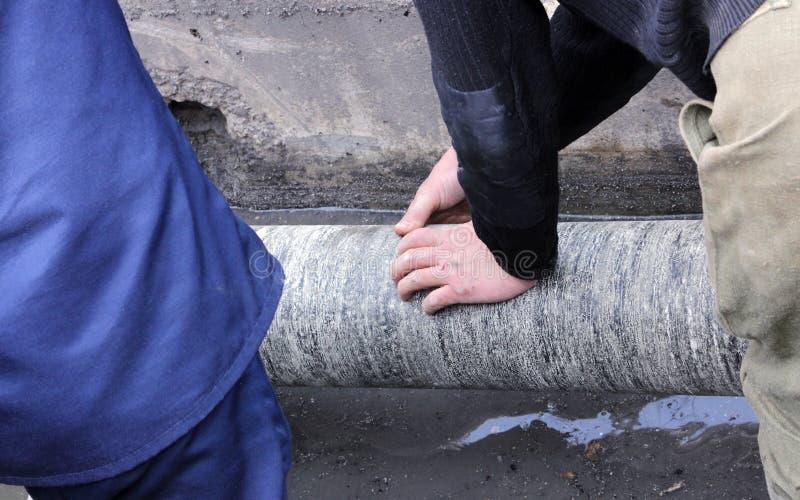 de arbeiders isoleren waterpijpenruberoid tijdens het reparatiewerk royalty-vrije stock afbeelding